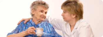caregiver with an elderly woman holding a tea cup