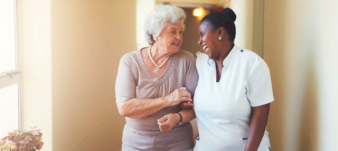 elderly woman assisted by a caregiver in hallway